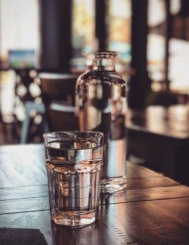 Flasche Wasser und ein Glas auf einem Tisch